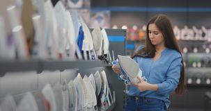 A mulher moreno bonita em uma camisa azul e em calças de brim escolhe um ferro em uma loja dos produtos eletrónicos de consumo vídeos de arquivo