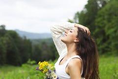 Mulher moreno bonita feliz no campo da camomila Foto de Stock Royalty Free