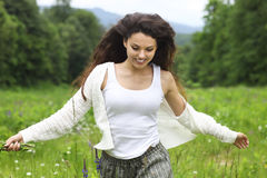 Mulher moreno bonita feliz no campo da camomila, real fêmea bonito fotografia de stock