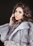 Mulher moreno bonita no casaco de pele do vison isolado na parte traseira do preto Foto de Stock