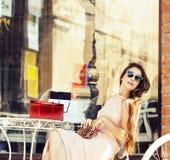 Mulher moreno bonita nova após o assento de compra no café fora no sorriso da rua fotografia de stock
