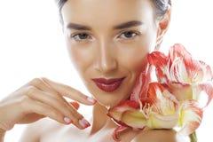 Mulher moreno bonita nova com fim vermelho da amarílis da flor isolada acima no fundo branco Composição extravagante da forma Imagem de Stock Royalty Free