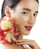 Mulher moreno bonita nova com fim vermelho da amarílis da flor isolada acima no fundo branco Composição extravagante da forma Foto de Stock Royalty Free