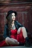 Mulher moreno bonita nova com o levantamento curto vermelho do vestido e do chapéu negro sensual no cenário do vintage Senhora mi Foto de Stock