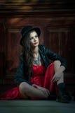 Mulher moreno bonita nova com o levantamento curto vermelho do vestido e do chapéu negro sensual no cenário do vintage Senhora mi Fotografia de Stock Royalty Free