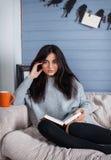 Mulher moreno bonita nova com a xícara de café que senta-se em casa no sofá pela janela Foto de Stock Royalty Free