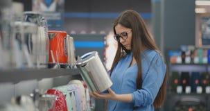 A mulher moreno bonita nova escolhe uma chaleira elétrica comprar Inspeciona o dispositivo, examina os preços e filme