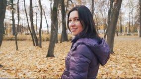 A mulher moreno bonita nova feliz está levantando com o ramalhete das folhas de outono no parque vídeos de arquivo