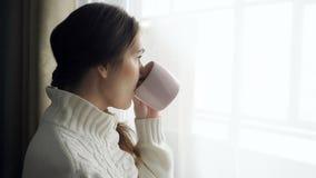 Mulher moreno bonita nova na xícara de café bebendo da camiseta perto da janela imagens de stock