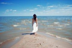 Mulher moreno bonita nova no vestido branco no litoral imagem de stock royalty free