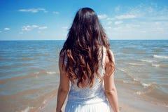 Mulher moreno bonita nova no vestido branco no litoral foto de stock
