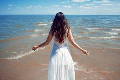 Mulher moreno bonita nova no vestido branco no litoral imagens de stock royalty free