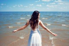 Mulher moreno bonita nova no vestido branco no litoral imagens de stock