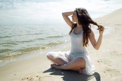 Mulher moreno bonita nova no vestido branco no litoral, sentando-se na areia e nos olhares no horizonte fotografia de stock