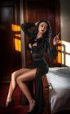 Mulher moreno bonita nova no vestido preto que relaxa no no cenário do vintage Jovem senhora misteriosa romântica Foto de Stock Royalty Free