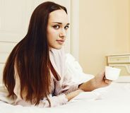 Mulher moreno bonita nova que coloca na cama, interior branco luxuoso foto de stock