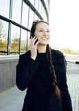 Mulher moreno bonita nova que fala no telefone que sorri na frente da construção moderna, executivos do conceito do estilo de vid Foto de Stock