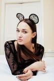 Mulher moreno bonita nova que veste as orelhas de rato 'sexy' do laço, colocando o sonho de espera na cama Imagem de Stock Royalty Free
