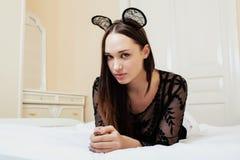 Mulher moreno bonita nova que veste as orelhas de rato 'sexy' do laço, colocando o sonho de espera na cama Foto de Stock Royalty Free