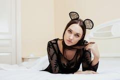 Mulher moreno bonita nova que veste as orelhas de rato 'sexy' do laço, colocando o sonho de espera na cama Fotografia de Stock