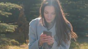 A mulher moreno bonita nova senta-se na grama no parque da mola e lê-se uma mensagem no telefone celular filme