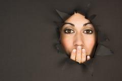 A mulher moreno bonita olha através das tampas rasgadas da mão do furo Fotografia de Stock Royalty Free
