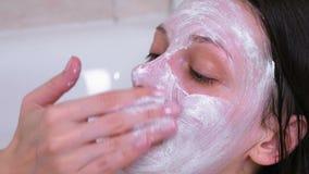 A mulher moreno bonita põe uma máscara sobre a cara que encontra-se no banheiro em casa Enfrente o close-up