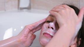 A mulher moreno bonita põe uma máscara sobre a cara que encontra-se no banheiro em casa Enfrente o close-up filme
