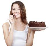 Mulher moreno bonita que come o bolo de chocolate Foto de Stock Royalty Free