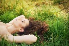 Mulher moreno bonita que encontra-se no gramado fresco Imagem de Stock