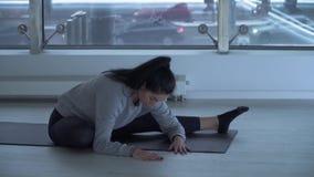 Mulher moreno bonita que estica seus pés que sentam-se na esteira da ioga no fitness center moderno com grande do chão ao teto video estoque