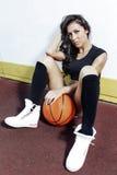 Mulher moreno bonita que joga o basquetebol no sol exterior da corte Fotos de Stock Royalty Free