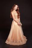 Mulher moreno bonita que levanta no vestido dourado longo sobre Foto de Stock