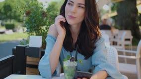 Mulher moreno bonita que senta-se no restaurante exterior e que usa seu telefone celular filme