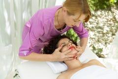 Mulher moreno bonita que toma a massagem principal Imagem de Stock