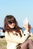 Mulher moreno bonita que toma notas em uma almofada, acampando Fotografia de Stock Royalty Free
