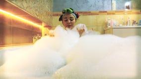 Mulher moreno bonita que toma o banho espumoso e que joga com espuma do sabão vídeo 4K filme