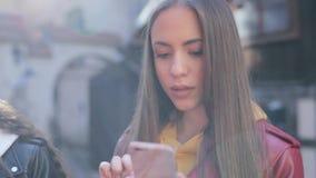 Mulher moreno bonita que usa o smartphone, alargamento solar no quadro Conceito m?vel da energia da tecnologia e da luz solar filme