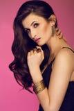 Mulher moreno bonita sensual que levanta no jewlery preto do vestido e do ouro que olha a câmera Menina com cabelo curly longo Fotografia de Stock