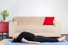 Mulher moreno caucasiano bonita na roupa preta na ioga azul imagem de stock royalty free