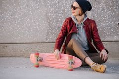 Mulher moreno clara feliz nova que senta-se com skate em um assoalho da rua fotografia de stock royalty free