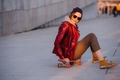 Mulher moreno clara feliz nova que senta-se em seu skate em uma cidade imagem de stock royalty free