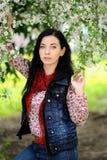 Mulher moreno com cabelo longo sob a árvore de florescência Foto de Stock