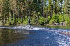 Mulher moreno consideravelmente magro dos jovens no wakeboard da equitação do roupa de mergulho sobre foto de stock royalty free