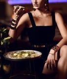 A mulher moreno da forma 'sexy' bonita no restaurante interior caro come ostras foto de stock