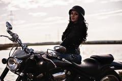 Mulher moreno da motocicleta bonita com uma motocicleta clássica c imagens de stock