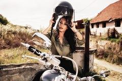 Mulher moreno da motocicleta bonita com uma motocicleta clássica c fotografia de stock