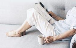 Mulher moreno de meia idade no compartimento cinzento da leitura do sof? com x?cara de caf? fotografia de stock