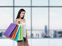 Mulher moreno de sorriso bonita com os sacos de compras coloridos das lojas extravagantes Fotos de Stock Royalty Free