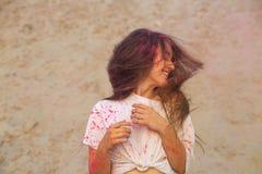Mulher moreno de sorriso gloriosa com o levantamento de vibração do cabelo coberto com a pintura seca de Holi fotografia de stock royalty free